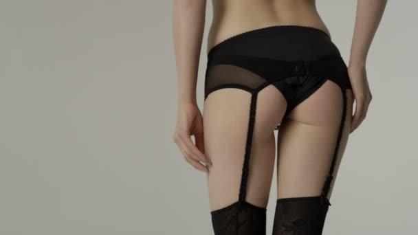 Unerkennbares Porträt einer jungen Frau in schwarzer Unterwäsche im Studio.