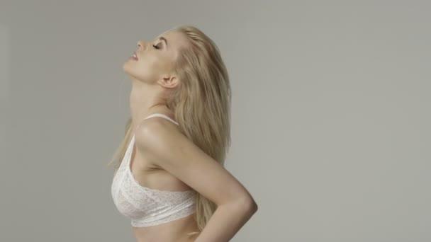 Portrait of a beautiful sexy blonde woman wearing white underwear posing in studio.