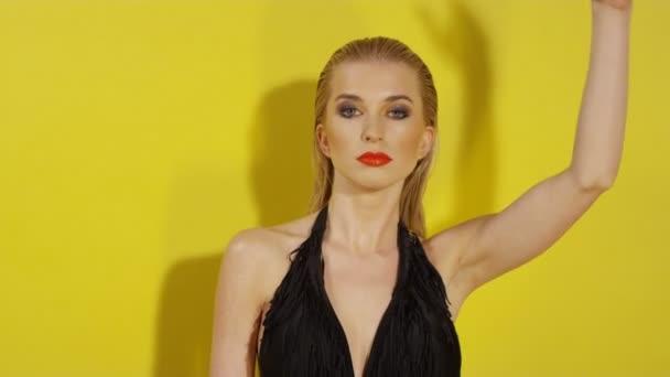 Krásná mladá žena pózuje v černých plavkách na žlutém pozadí