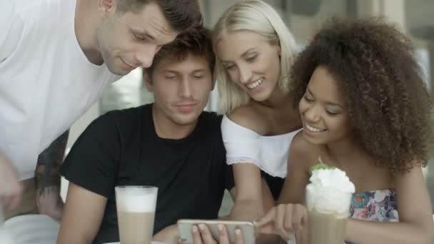 Gruppo di amici guardando le foto sul cellulare e che ridono.
