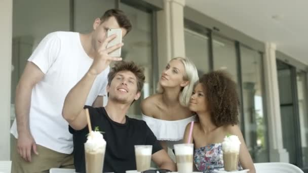 Group of young people sitting in a restaurant and taking a selfies.