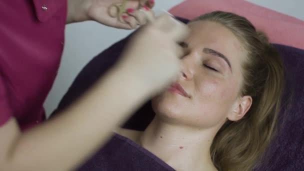 closeup kosmetička rukou pomocí pinzety na obočí ženské v kosmetický salon
