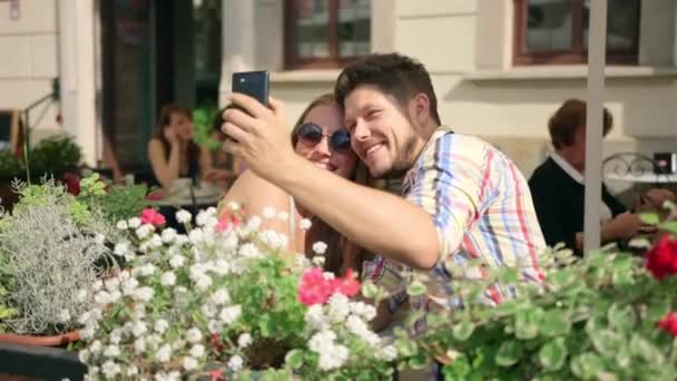 Young couple taking a selfie together on the cafe terrace on sunny day