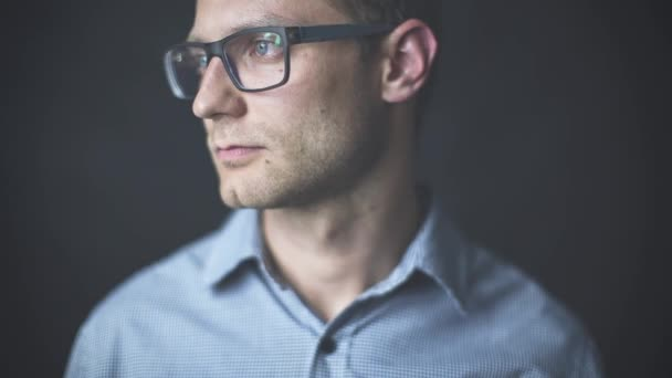 mladý atraktivní muž při pohledu na fotoaparát má vážný pohled izolovaných na černém pozadí