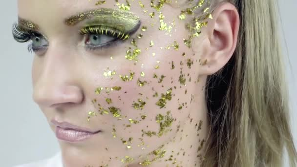 sexy kaukasische Frau mit Kunst goldenes Make-up posiert im Studio.