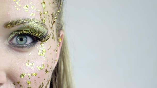 polovina tvář sexy kavkazské ženy s make-up umění zlatý pózuje ve studiu