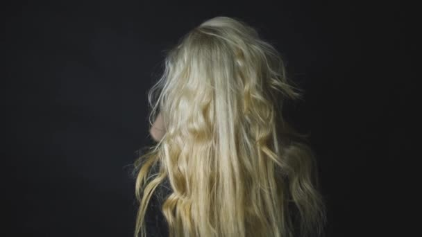 Woman touching her long curly blonde hair in black background. Rear view.