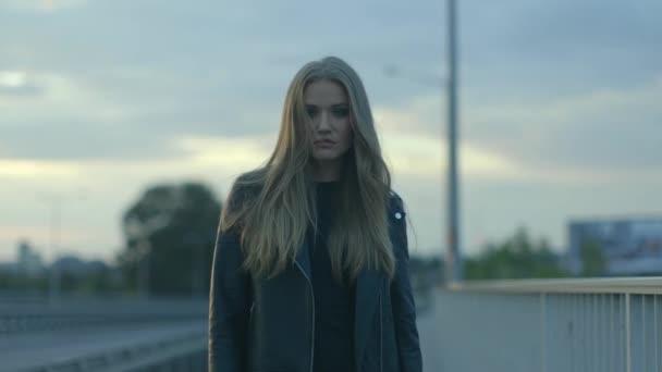 giovane e bella donna in una giacca in pelle in mezzo alla strada
