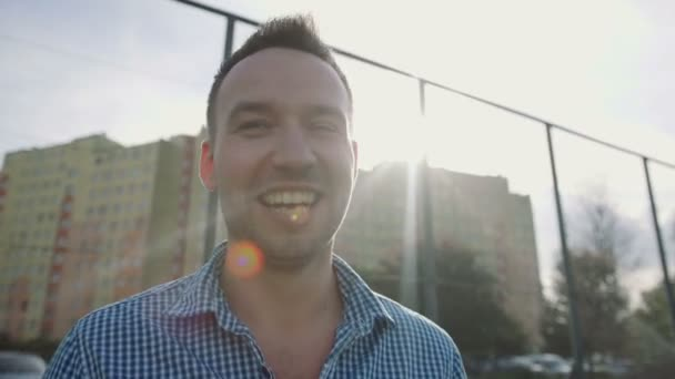Pohledný muž s úsměvem moderní plot zdi, venkovní.