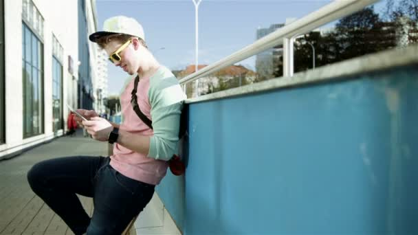 Young stylish teenager using tablet in a city street during sunny day.