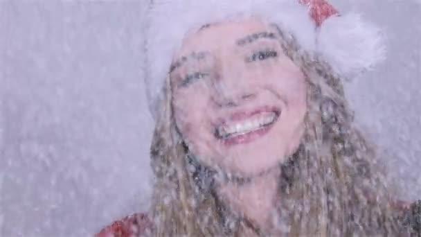 A szép lány a santa claus kalap, fa ágai élvezi esik a hó