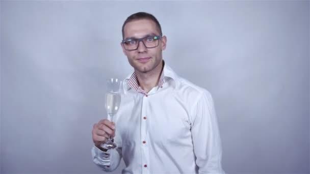 Mladý pohledný muž v bílé košili oslavit šampaňským šedé pozadí