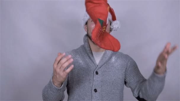 Happy man in Santa Claus hat with christmas gift. Slow motion.