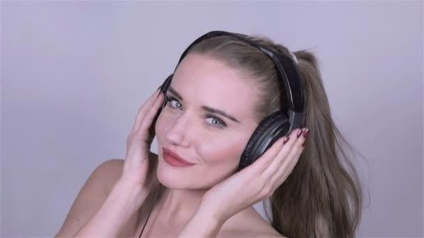 Sexy Kavkazský žena se sluchátky, poslech hudby, zpomalené