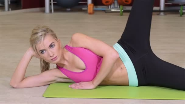 Young beautiful fitness girl exercising in the gym on a mat.