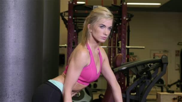 Krásné fit žena, která dělá cvičení s činkami v tělocvičně