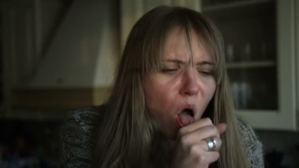 Sick woman in the kitchen blowing nose in paper tissue.