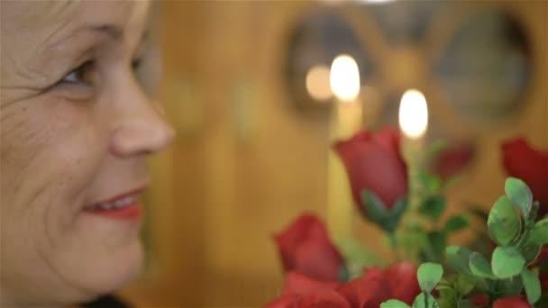 Zralá žena drží velkou kytici rudých růží a s úsměvem
