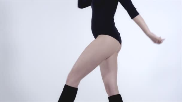 Legs of a modern dancer with black body costume wearing knee-highs.