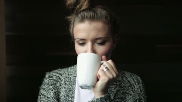 Žena doma pití kávy nebo čaje a usmívá se na kameru