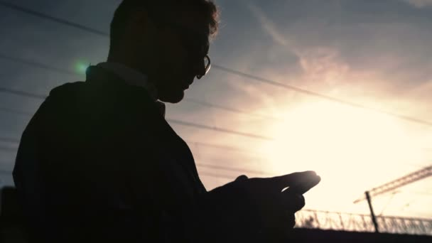 Portrait of handsome young man sending a text message while standing outside.