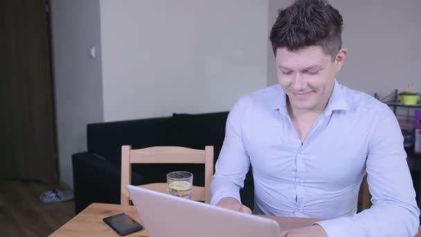 Boldog, mosolygós, fiatal ember dolgozik, és gépelés-ra laptop otthon