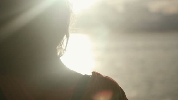 Close up of silhouette of young woman on the sunset. Rear view.