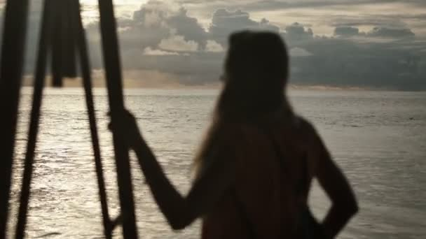 Silueta mladé ženy, na západ slunce. Zadní pohled