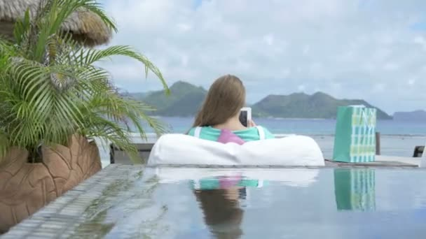 Woman in hotel lounge using digital tablet during vacation, outdoors.