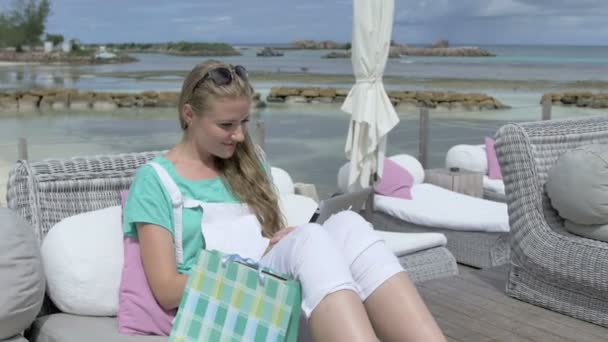 Attractive woman in deckchair using digital tablet during vacation.