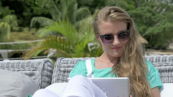 Woman sitting in lounger using digital tablet during vacation.