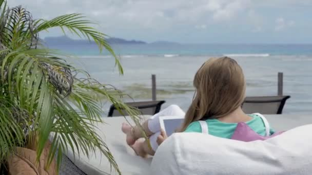 Woman in deckchair using digital tablet during exotic vacation.