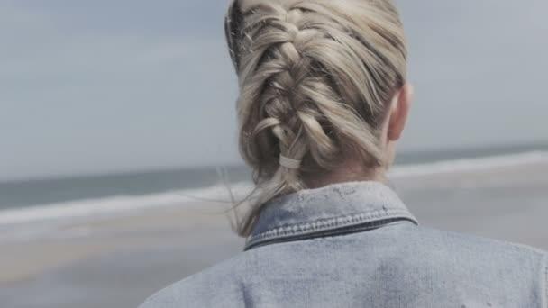 Šťastná mladá žena v džínové bundě úsměv do kamery na opuštěné pláži