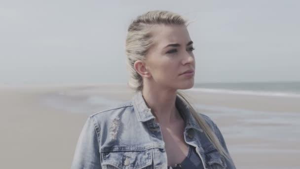 Zamyšlená dívka v džínové bundě relaxační na opuštěné pláži