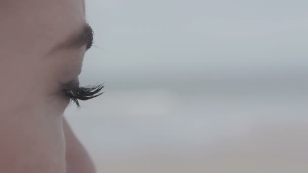 Close up of young womans eye looking on lonely beach.