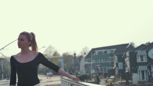 Mladá žena ve městě Zaanse Schans v Holandsku stojí na mostě a do kraje