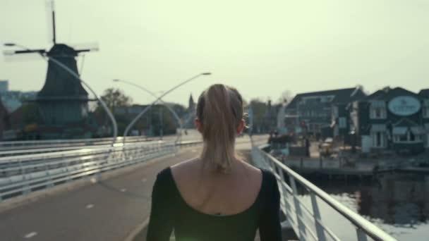 Pohled zezadu na ženské siluety běží při západu slunce na mostě v Holandsku, zpomalené