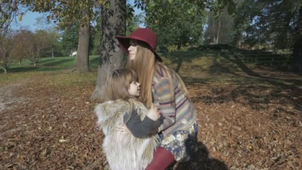 Little girl having fun with her mom in the autumn park.
