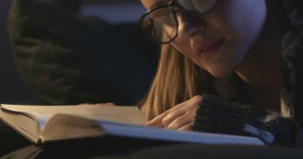 Krásná mladá žena s knihou vleže na gauči