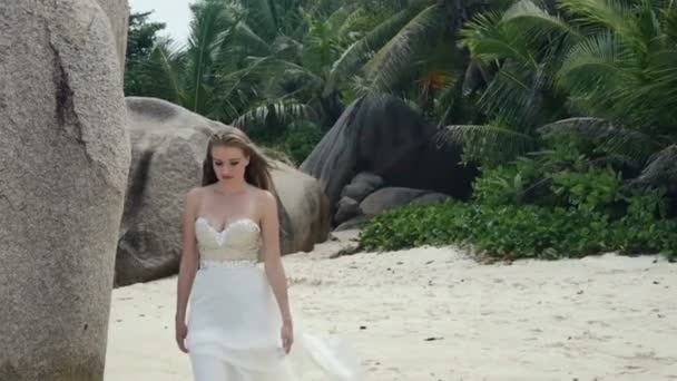 Young bride in luxury dress relaxing on a tropical beach.