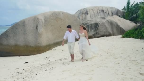 Just-married couple walking on tropical beach and kissing.