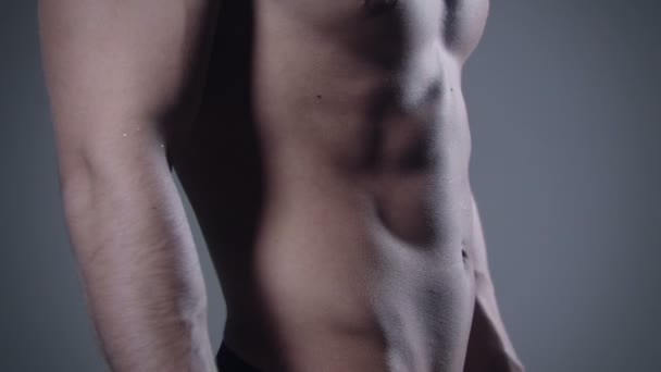 Close up of muscular male body on grey background.