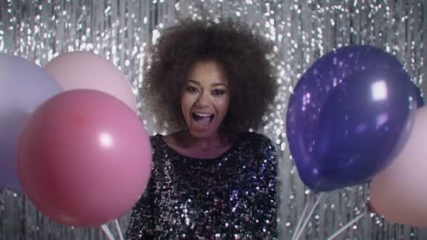Afro americký vzrušená žena držící parta barevných balónků ve studiu.