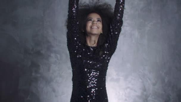 Beautiful black woman throwing golden confetti, slow motion .