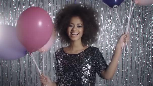 attraktive junge Frau mit Luftballons auf silbernem Glitzerhintergrund, lächelnd.