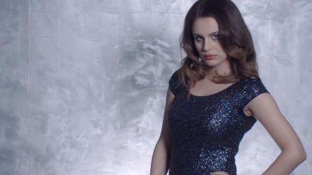 Krásná mladá dívka pózuje v elegantní šaty, při pohledu na fotoaparát.