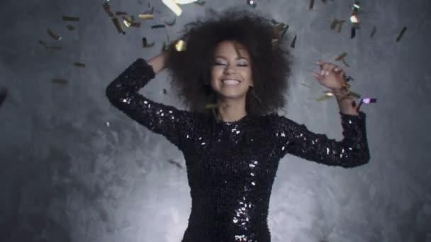 Beautiful black woman among golden confetti, slow motion .