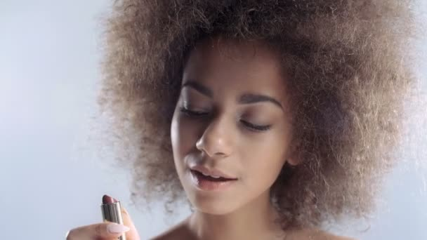 Portrait of a beautiful young African woman applying lipstick.