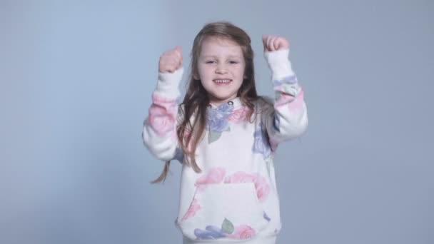 Portrét dívky krásné a sebevědomý zobrazující palce, studio
