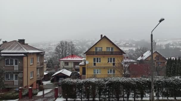 Limanowa, Jižní Polsko: široký úhel záběru střešních domů na polských horách proti pohybujícím se zataženým mrakům proudícím horskými kopci během zamrzlé zimy roku 2020 Vánoce